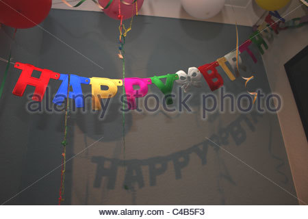 happy birthday hanging sign ; a-celebration-with-a-happy-birthday-banner-sign-hanging-on-the-ceiling-c4b5f3