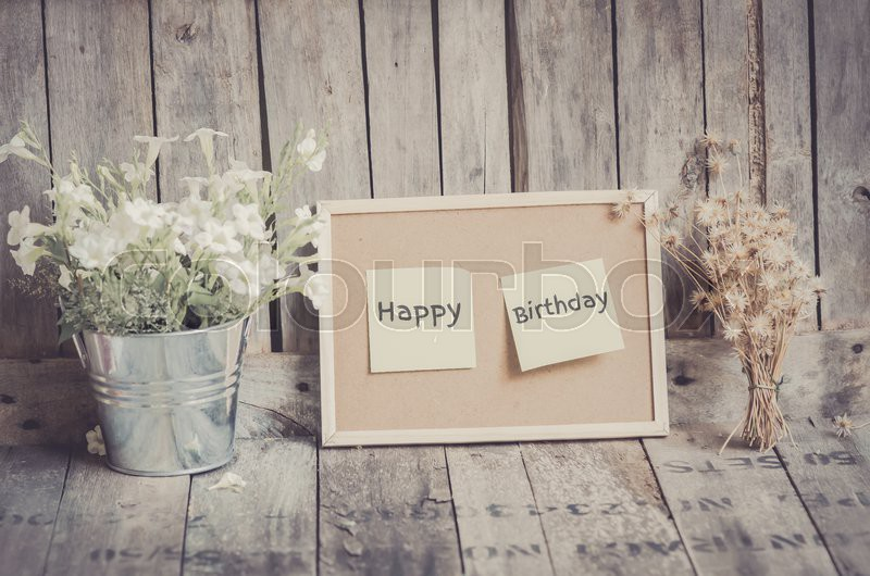 happy birthday wood ; 13043776-vintage-style-effect-happy-birthday-message-on-corkboard-with-flowers-by-wooden-background