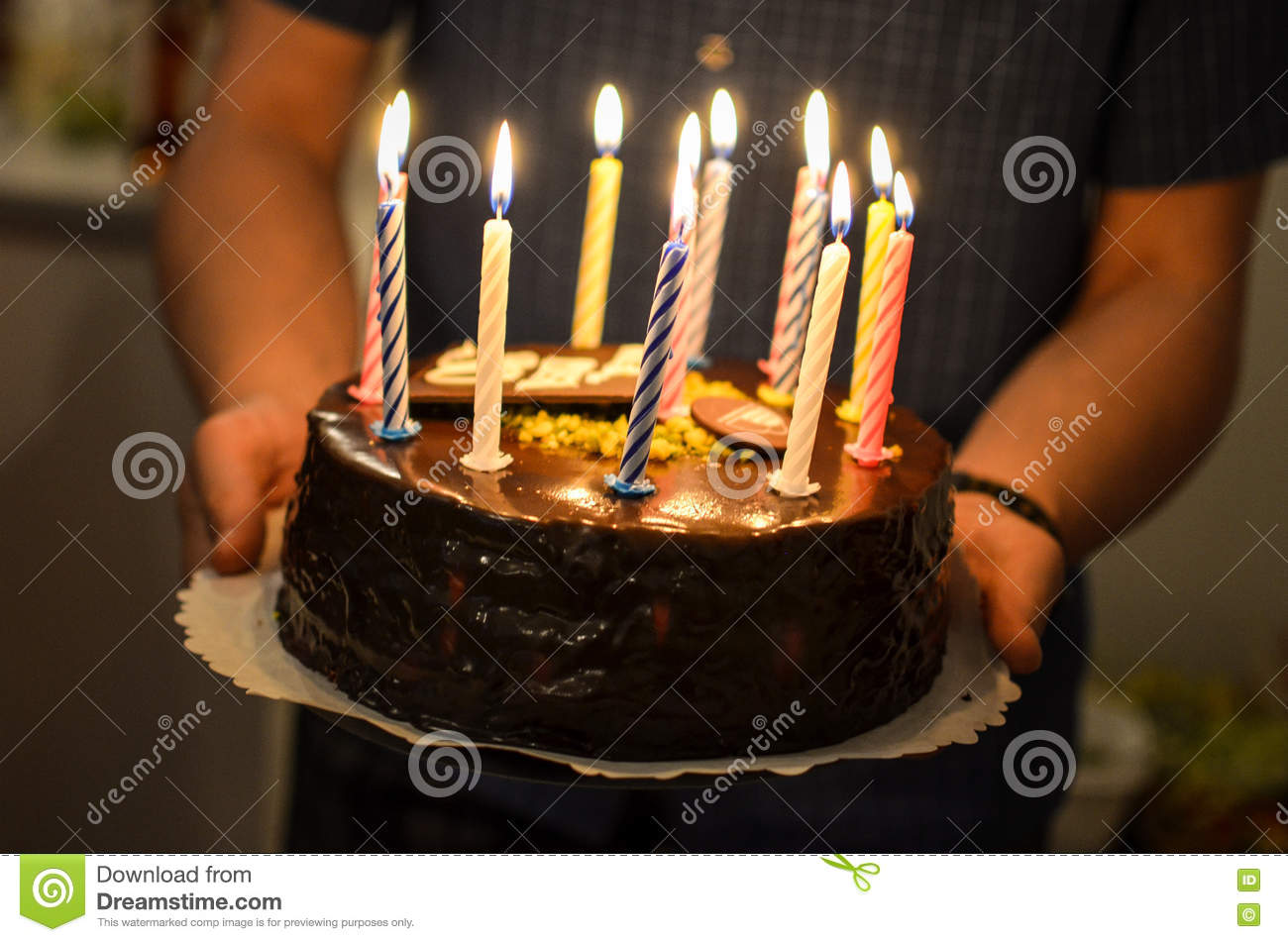 picture of birthday cake with burning candles ; birthday-cake-burning-candles-man-giving-73191265
