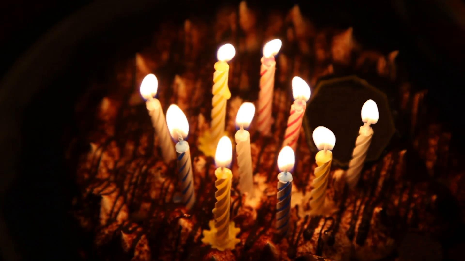 picture of birthday cake with burning candles ; happy-birthday-cake-with-burning-spiral-candles-which-are-then-extinguished_xjujovpto__F0000