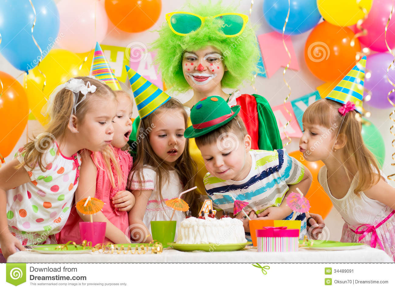 picture of birthday party celebration ; kids-clown-celebrating-birthday-party-blowing-candle-cake-34489091