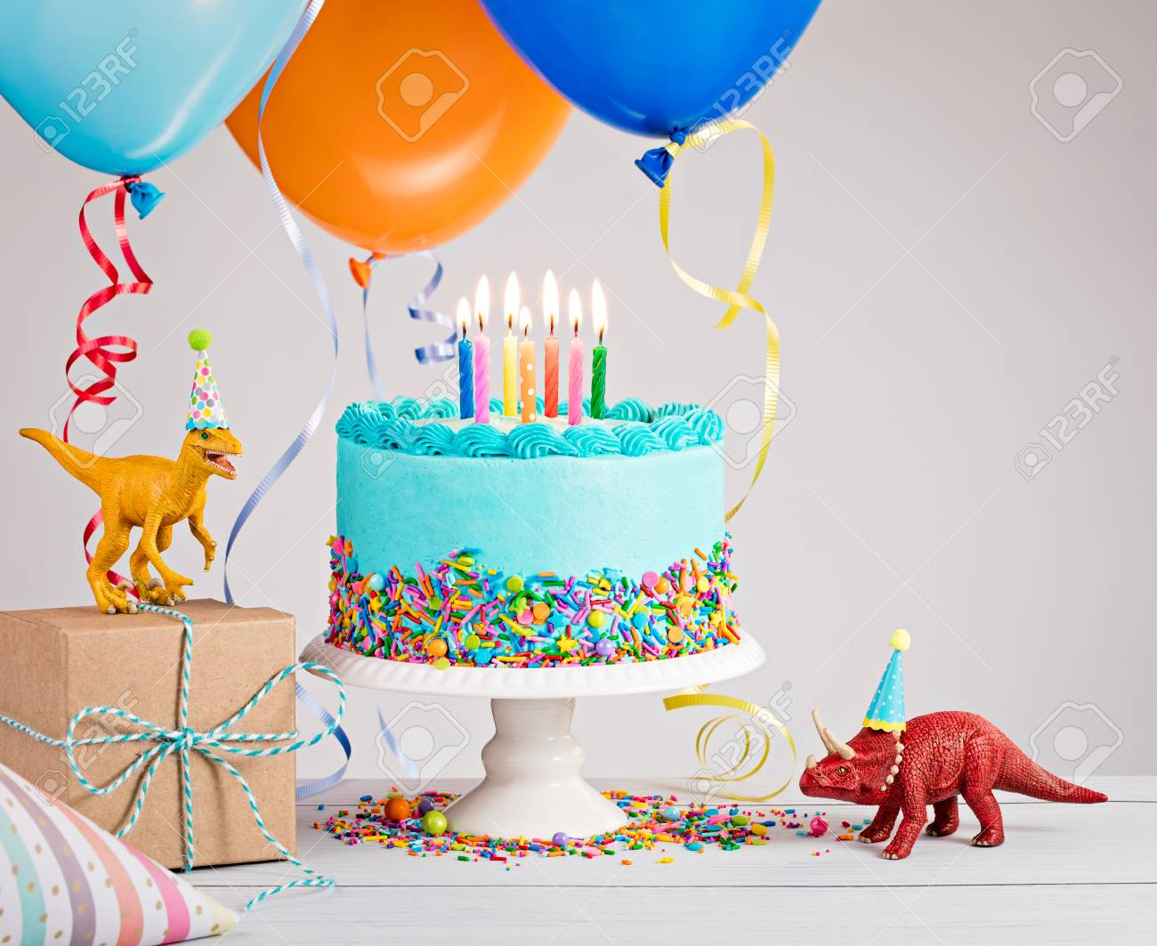 picture of birthday party scene ; 80428227-childs-birthday-party-scene-with-blue-cake-gift-box-toy-dinosaurs-hats-and-colorful-balloons-over-li