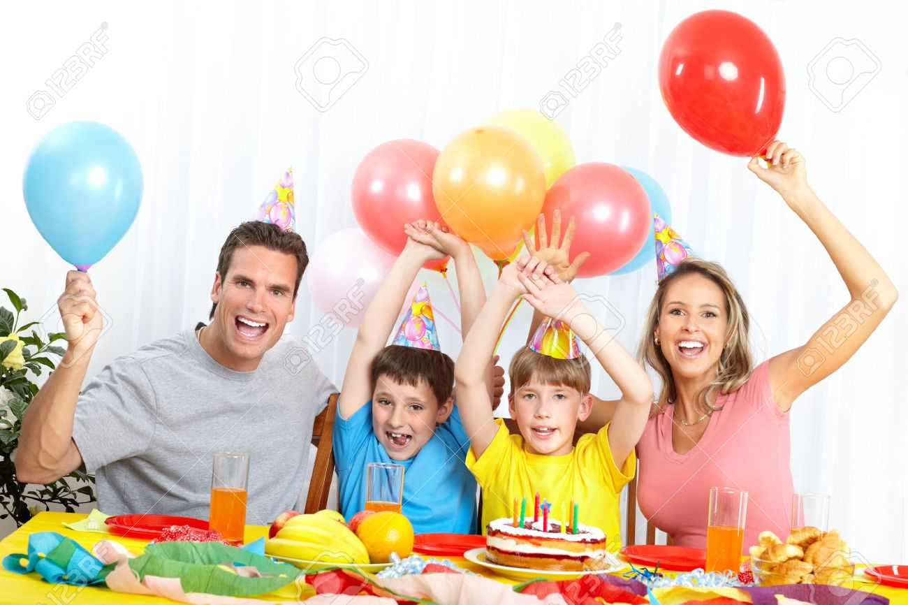stock image birthday ; 7088111-happy-family-father-mother-and-children-celebrating-birthday-at-home