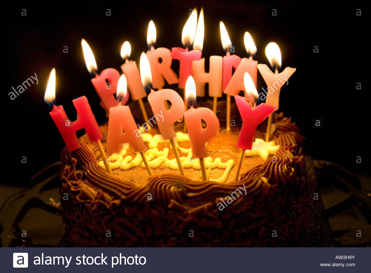 a picture saying happy birthday ; lighted-candles-saying-happy-birthday-on-a-chocolate-cake-AW3H9Y