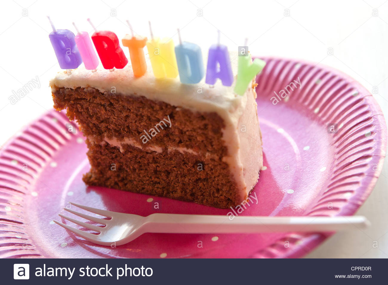 a piece of birthday cake ; a-slice-of-birthday-cake-with-birthday-candles-on-a-pink-paper-plate-CPRD0R