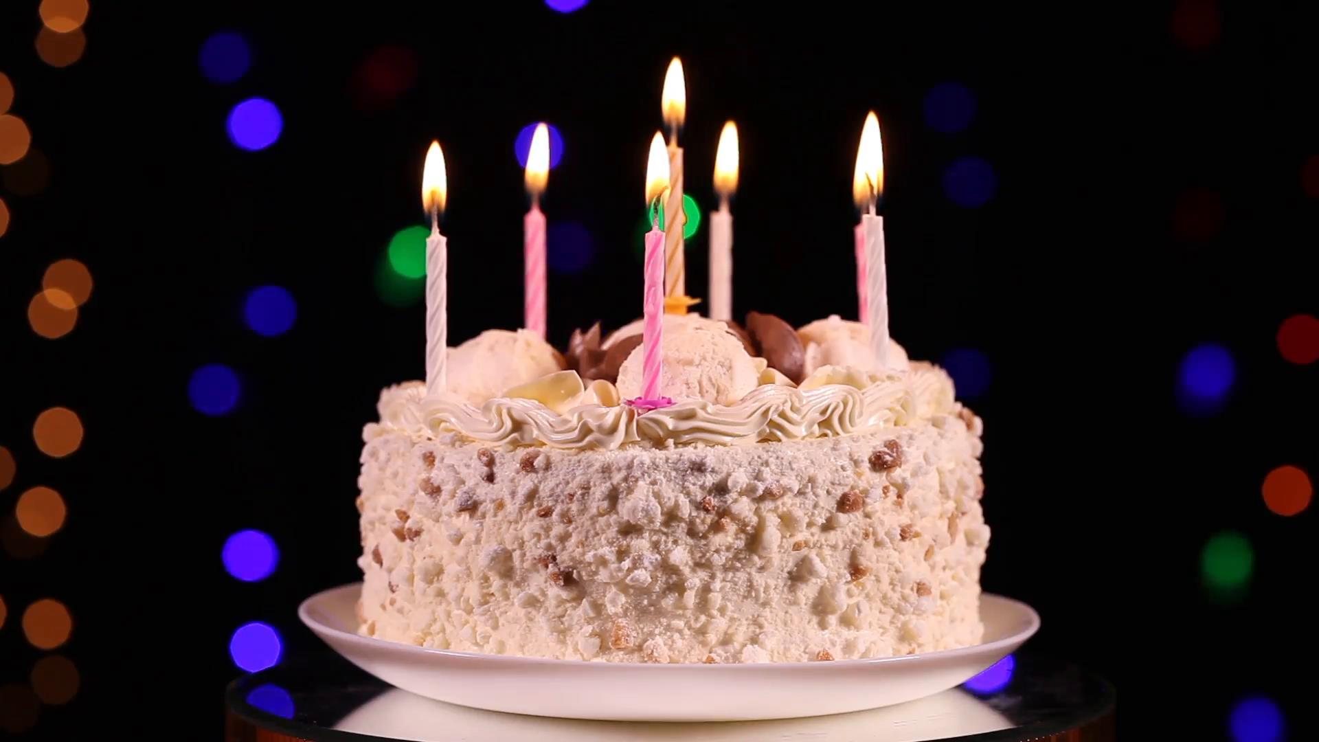 picture of birthday cake and candles ; happy-birthday-cake-with-burning-candles-in-front-of-black-background-with-flashing-lights_vagh2n9xnx__F0000