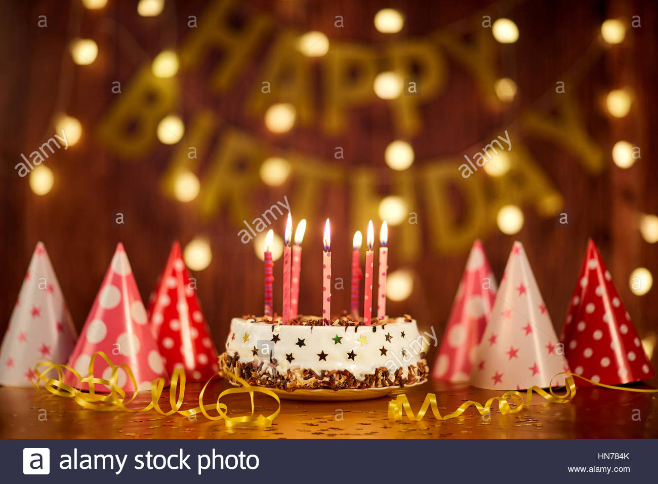 picture of birthday cake and candles ; happy-birthday-cake-with-candles-on-the-background-of-garlands-a-HN784K