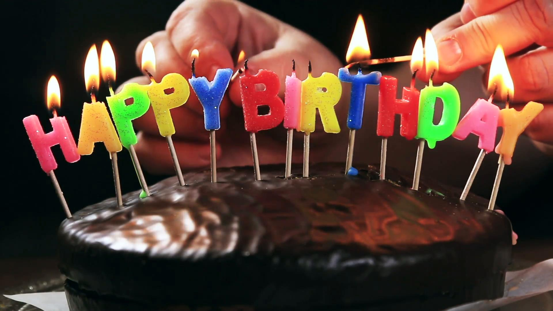 picture of birthday cake and candles ; lighted-candles-on-a-happy-birthday-cake-candles-with-the-words-happy-birthday-on-a-chocolate-cake-hand-lights-a-candle-happy-birthday-time-lapse_rgfcpc0e__F0009