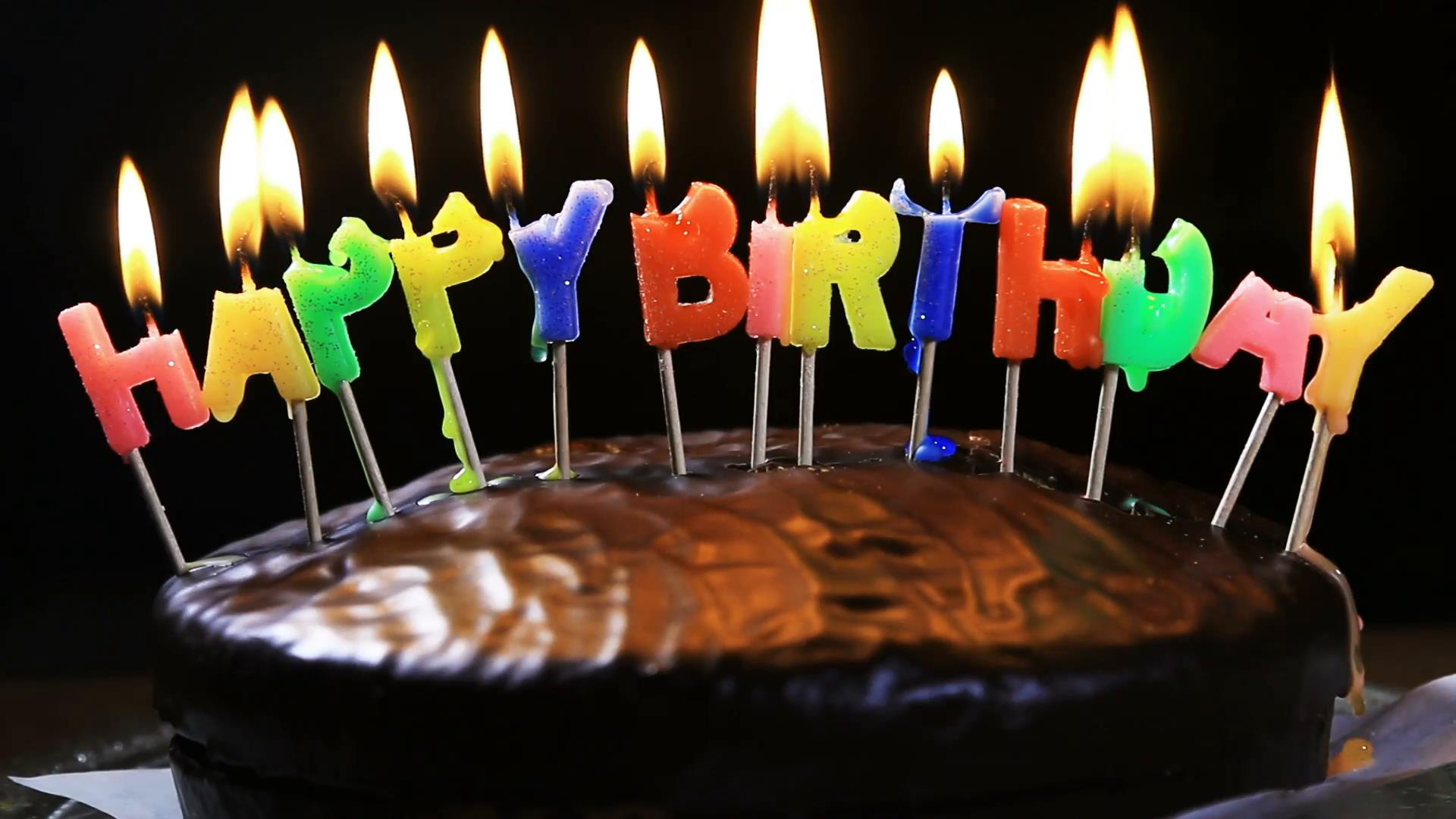 picture of birthday cake and candles ; lighted-candles-on-a-happy-birthday-cake-candles-with-the-words-happy-birthday-on-a-chocolate-cake-hand-lights-a-candle-happy-birthday_rz7gcacv__F0009